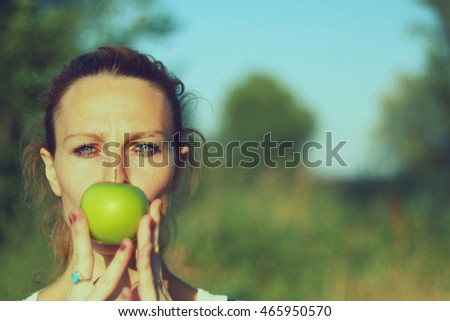 Woman covering her mouth with an healthy green apple on a sunny day in nature.