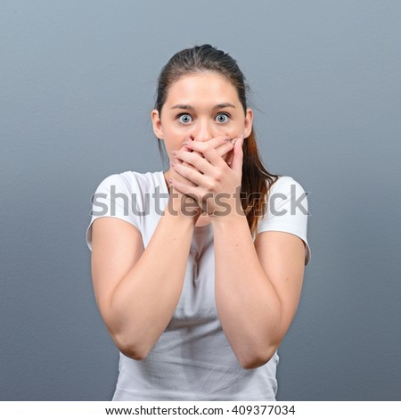 Woman covering her mouth with hands against  gray background - stock photo