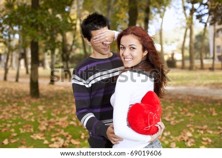 woman covering the eyes to his boyfriend holding a red heart behind her back (selective focus with shallow DOF) - stock photo
