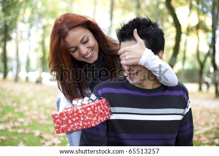 woman covering the eyes to his boyfriend with giving him a present (selective focus with shallow DOF) - stock photo