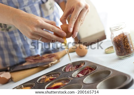 Woman cracking an egg into, making paleolithic muffins for breakfast - stock photo