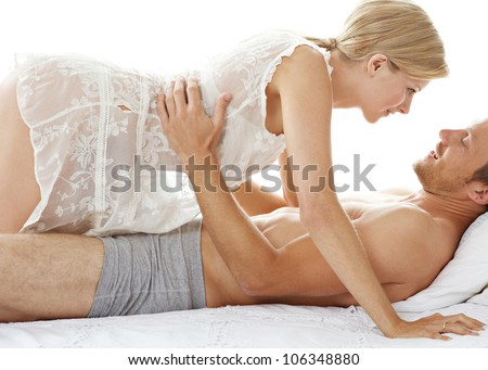 Woman crawling over man in bed, being playful and smiling. - stock photo