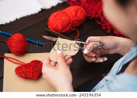 Woman creating red woolen heart - stock photo