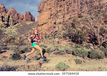 Woman cross country running in mountains. Beauty female runner jogging and training with backpack outdoors in nature, trail running on rocky path on Tenerife with Teide in background, Canary Islands. - stock photo