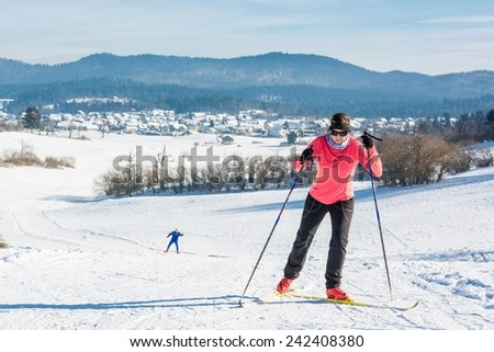 Woman cross country skiing. Ascending a slope with another skier following. - stock photo