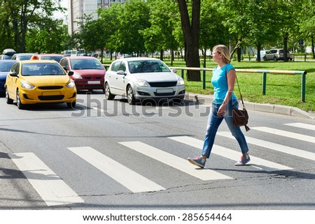 Woman crossing the street at a pedestrian crossing - stock photo