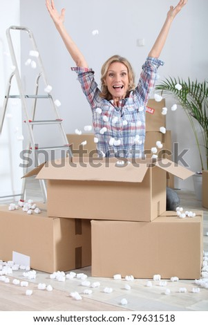 Woman crouching in front of stacked cardboard boxes - stock photo