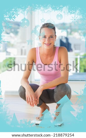 Woman crouching on weighing scale in gym against christmas frame - stock photo