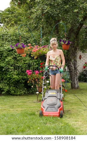 Woman cut the flower garden with an electric mower