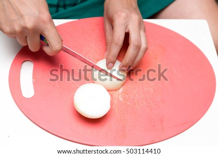 woman cuts onion knife