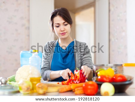 woman cuts red pepper at her kitchen   - stock photo