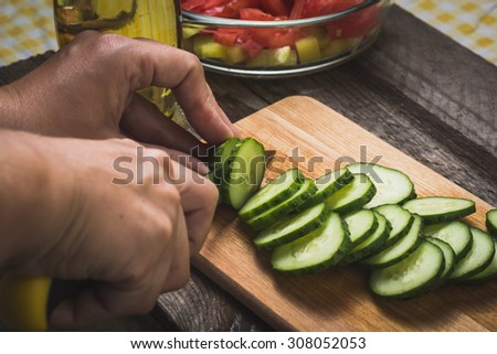Woman cuts slice vegetables cucumbers