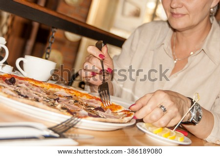 woman cuts the pizza in the cafe