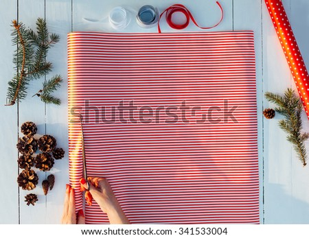 Woman cutting decorative paper for gift-wrapping - stock photo