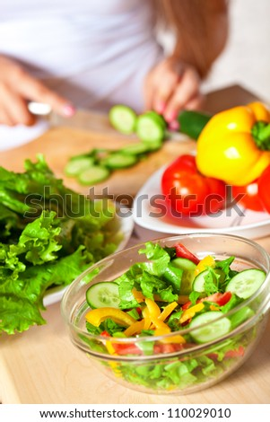 woman cutting  fresh green cucumber for salad - stock photo