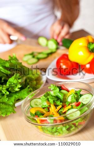woman cutting  fresh green cucumber for salad - stock photo