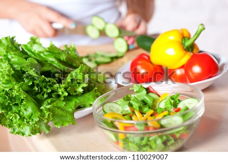 woman cutting  fresh green cucumber for salad, horizontal