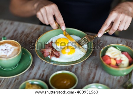 Woman cutting fried eggs with golden fork and knife at breakfast - stock photo