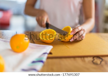 Woman cutting oranges on a wood kitchen table