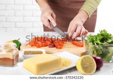Woman cutting smoked salmon for salad, at kitchen