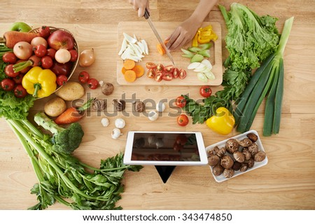 Woman cutting vegetables for the dish, view from above - stock photo
