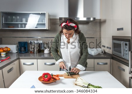 Woman cutting vegetables in wooden table in the kitchen