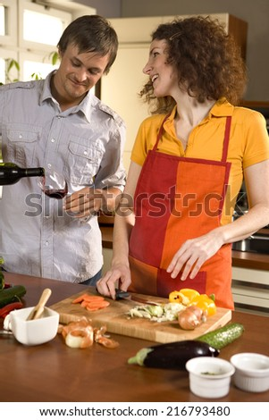 Woman cutting vegetables, man pouring wine. - stock photo