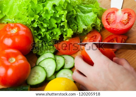 Woman cutting vegetables (tomato, cucumber, salad) on a wooden table - stock photo