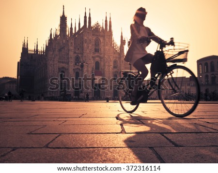 Woman cycling in Milan - stock photo