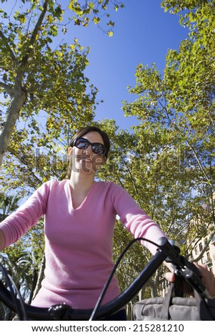 Woman cycling in park, smiling, portrait, front view, low angle view - stock photo