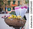 Woman cycling on  Hanoi Road with  sell flower - stock photo