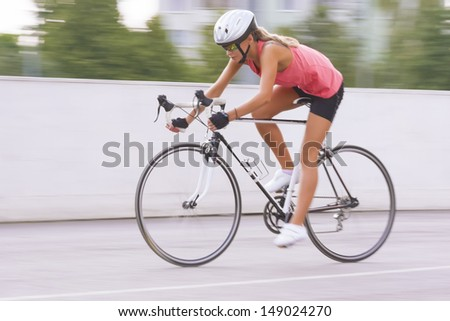 woman cycling outdoors. panning technique used.horizontal shot - stock photo