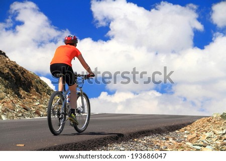 Woman cyclist ascending a mountain road to the sky and clouds