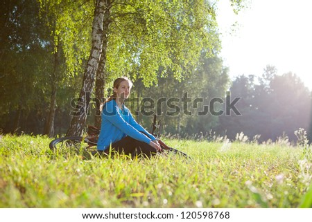 Woman cyclist enjoying relaxation in spring sunny park sitting in the fresh green grass near a birch trunk - stock photo