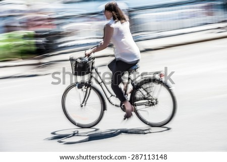 Woman cyclist in city traffic - stock photo