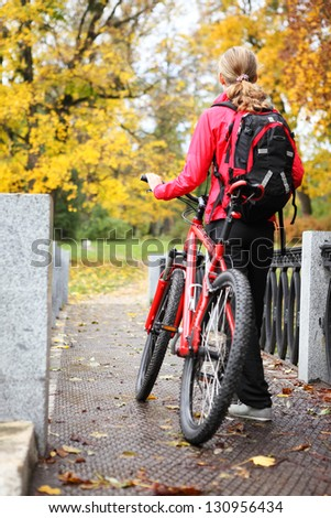 Woman cyclist with bike and backpack bicycle walk in autumn park - stock photo