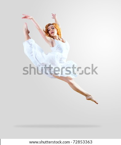 Woman dancer jump posing on background