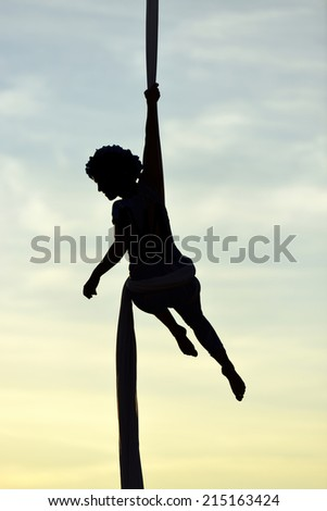 woman dancer on aerial silk, aerial contortion, aerial ribbons, aerial fabric in posing exercise - stock photo
