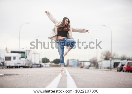 woman dancer on ballet tips, jeans and white coat on the street and movement