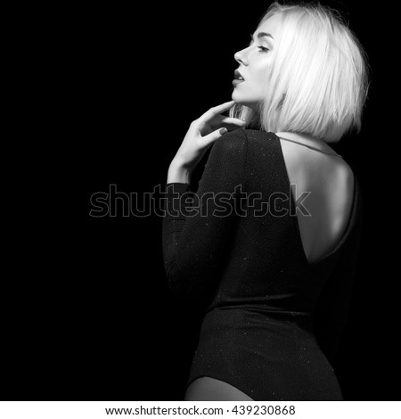 Woman dancer with short blond hair in shiny black body on a black background - stock photo