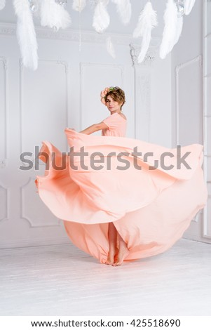 Woman dancing in pink evening dress flying on wind. Waving fabric, fashion shot - stock photo