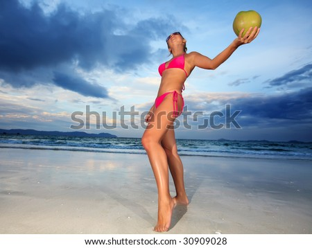 Woman dancing near the ocean with coconut. Focus on coconut
