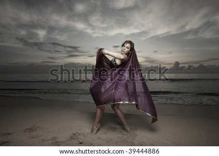 Woman dancing on the beach during sunrise - stock photo