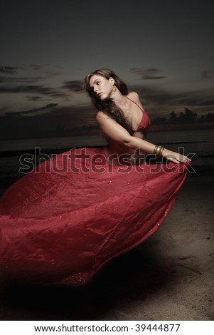 Woman dancing on the beach with a red silk veil - stock photo