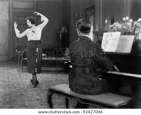 Woman dancing while her husband is playing the piano