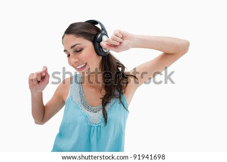 Woman dancing while listening to music against a white background