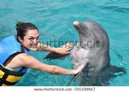 woman dancing with dolphin in blue pool water