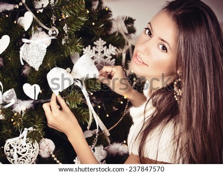 Woman decorating christmas tree. Fashionable luxury girl celebrating New Year. Beautiful luxury trendy brunette. Christmas holiday and New Year.  - stock photo