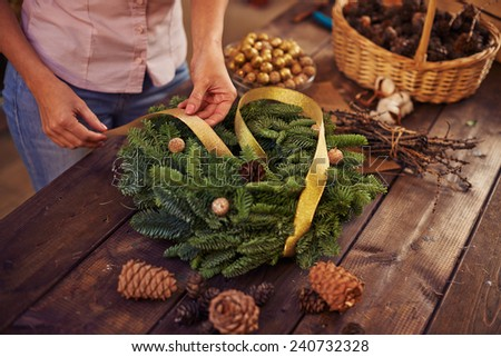 Woman decorating coniferous wreath - stock photo