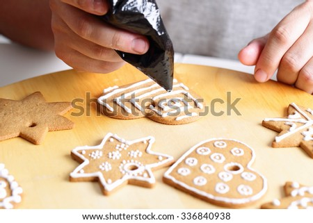 Woman decorating gingerbread cookies. Close up view with selective focus. - stock photo